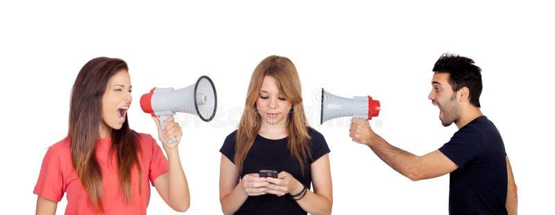 Kvinna och män med en megafon som ropar en vän med en mobil royaltyfri fotografi