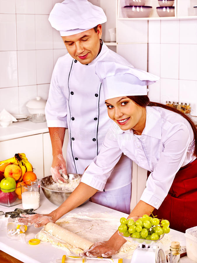 Kvinna och man i deg för kockhattmatlagning royaltyfria bilder