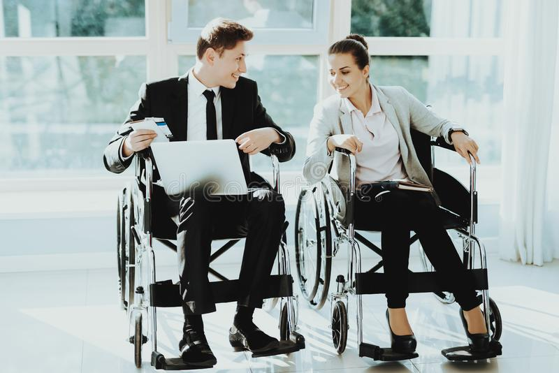 Kvinna och man i rullstolar i affärskläder arkivbild