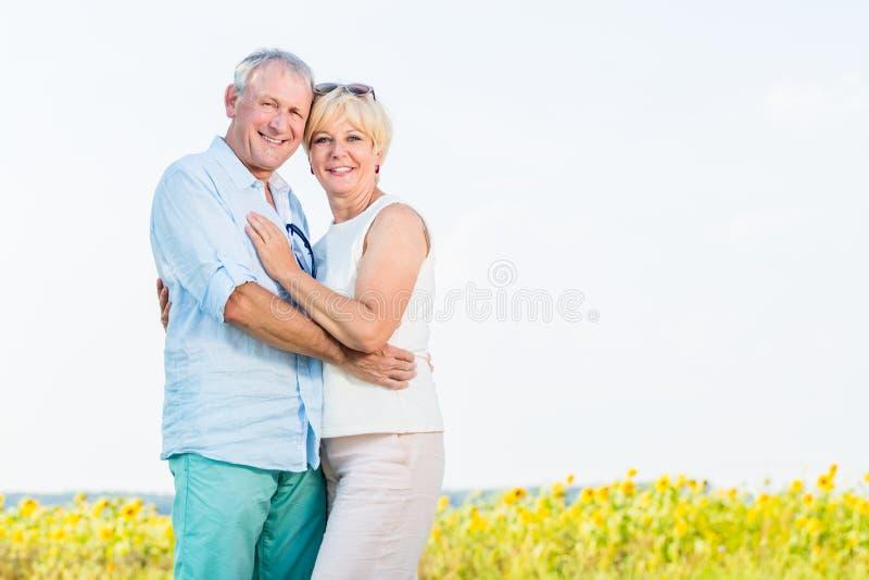 Kvinna och man, pensionärer, omfamna som är förälskat royaltyfri foto