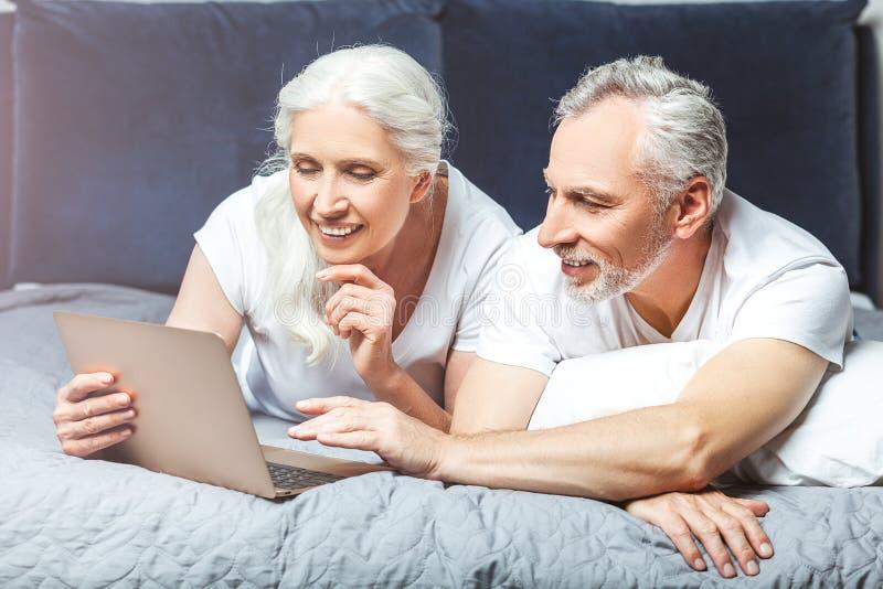 Kvinna och man som använder bärbara datorn i sängen royaltyfri fotografi