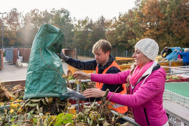 Kvinna och man som ger förlorad gräsplan i behållare på återanvändning av mitten arkivfoton