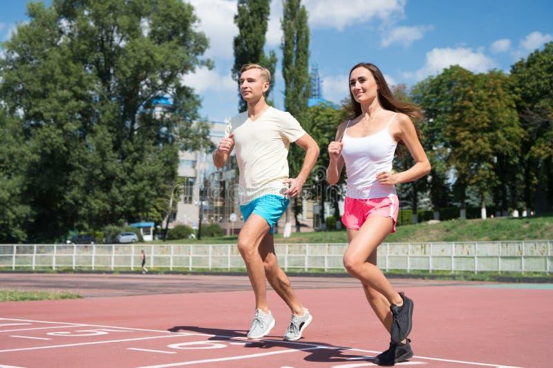 Kvinna och man som körs på stadion Par av löpare på soligt utomhus- Aktivitet och energi Utbildning och genomkörare på ny luft Sp arkivbild