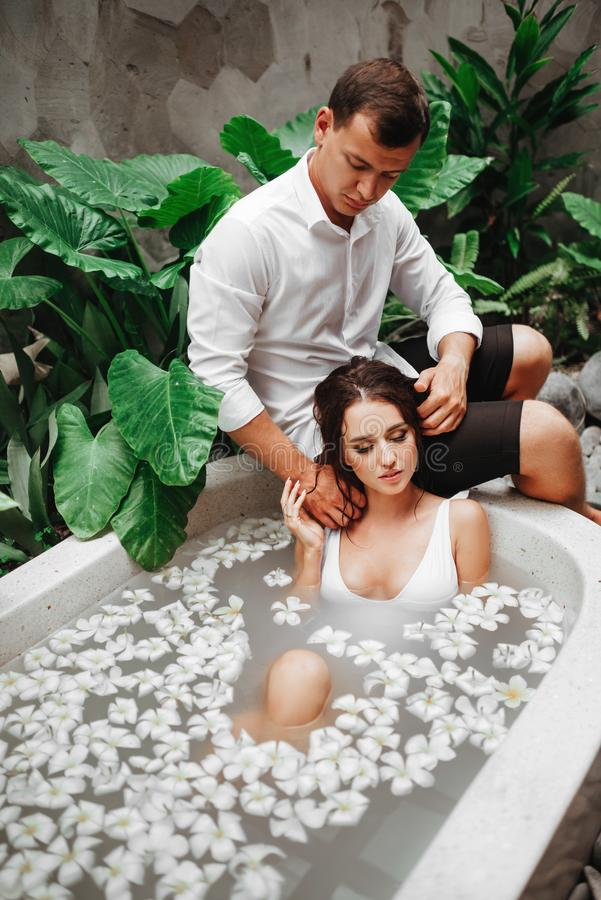 Kvinna och man som kopplar av i bad med tropiska blommor som är utomhus- på semesterorten för lyxigt hotell fotografering för bildbyråer