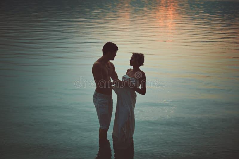 Kvinna och man som kramas i mörkt vatten royaltyfri foto