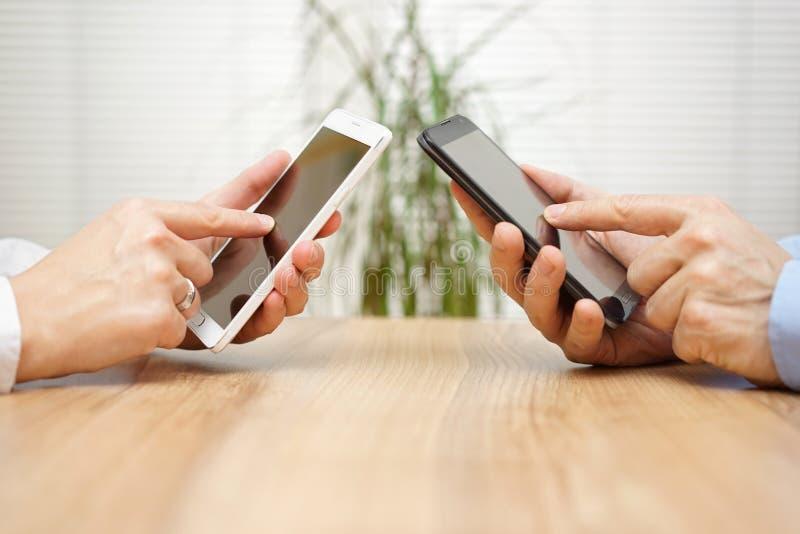 Kvinna och man som tillsammans använder applikationer på den smarta telefonen för mobil arkivbilder