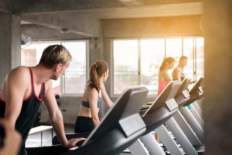 Kvinna- och manspring på trampkvarnar som tillsammans gör cardio utbildning i en idrottshall, sunt livsstilbegrepp royaltyfri bild