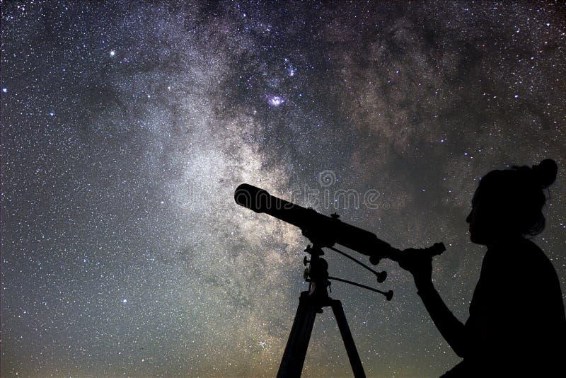 Kvinna och natthimmel Hålla ögonen på stjärnakvinnan med teleskopet royaltyfri bild