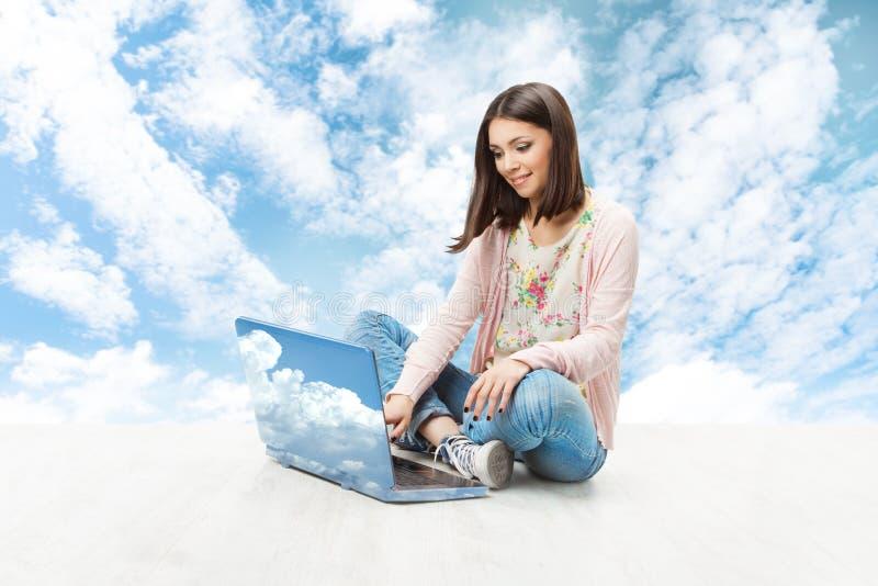 Kvinna- och radiobärbar datoranteckningsbok över himmel royaltyfri bild
