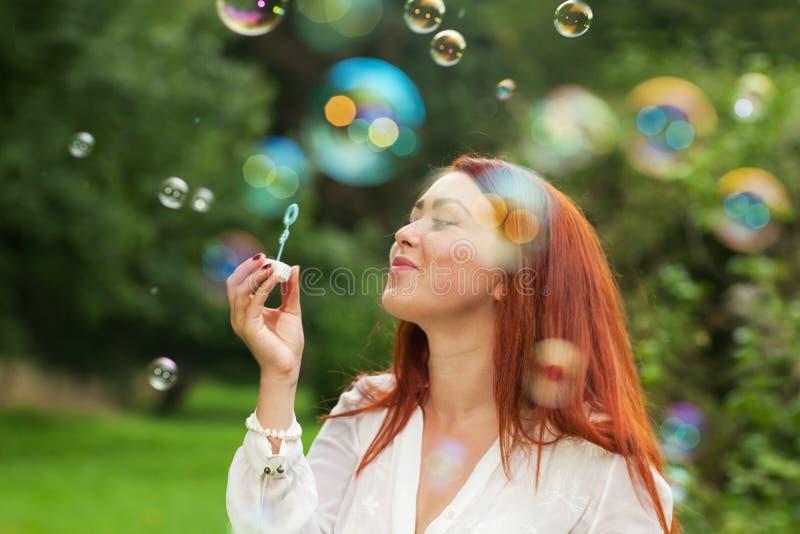 Download Kvinna och såpbubblor fotografering för bildbyråer. Bild av long - 76702479