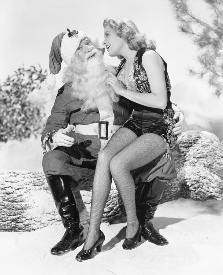 Kvinna och Santa Claus som sitter tillsammans att skratta (alla visade personer inte är längre uppehälle, och inget gods finns Le arkivfoto