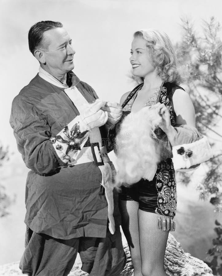 Kvinna och Santa Claus som talar och skrattar med de (alla visade personer inte är längre uppehälle, och inget gods finns supp royaltyfri foto