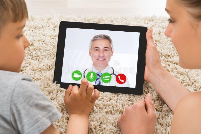 Kvinna- och sonvideoConferencing med doktor On Rug arkivfoton