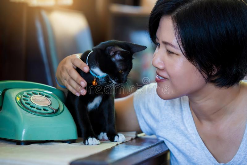 Kvinna och svart katt som sitter med den Retro roterande telefonen på trätabellen fotografering för bildbyråer