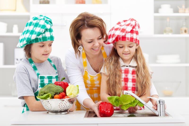 Kvinna och ungar som förbereder grönsakerna för ett mål royaltyfria foton