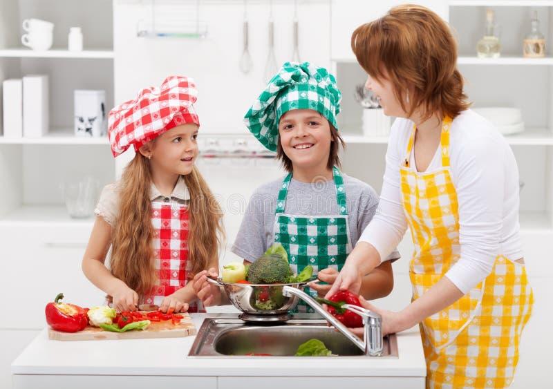 Kvinna och ungar som tvättar grönsaker i köket arkivbild