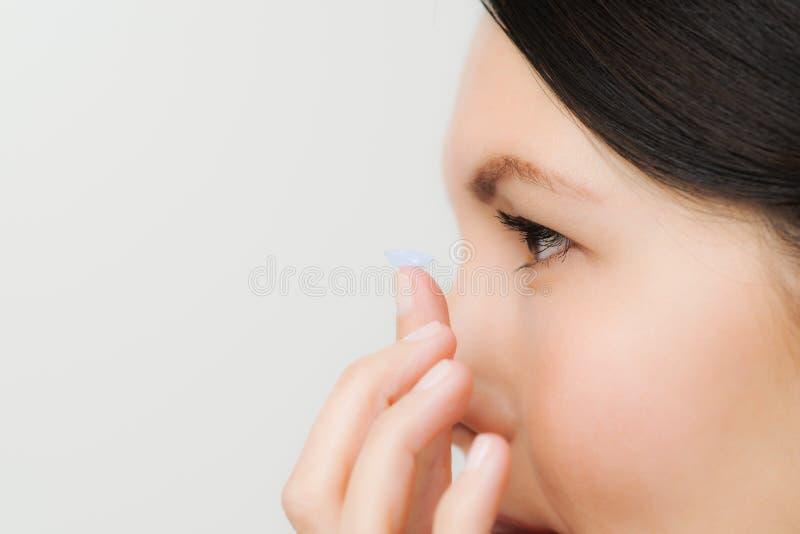 Kvinna omkring som förlägger en kontaktlins i hennes öga royaltyfri fotografi
