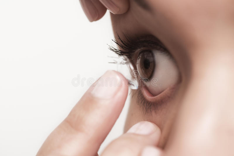 Kvinna omkring som förlägger en kontaktlins i hennes öga arkivbilder