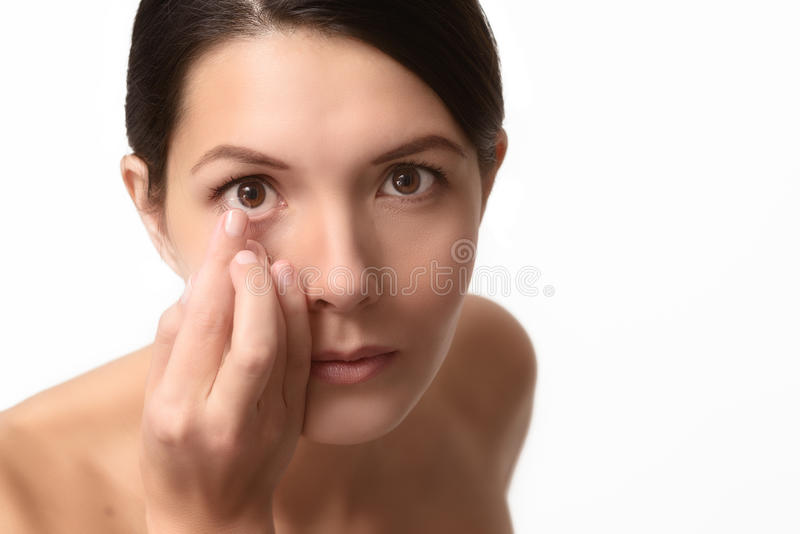 Kvinna omkring som förlägger en kontaktlins i hennes öga royaltyfria bilder