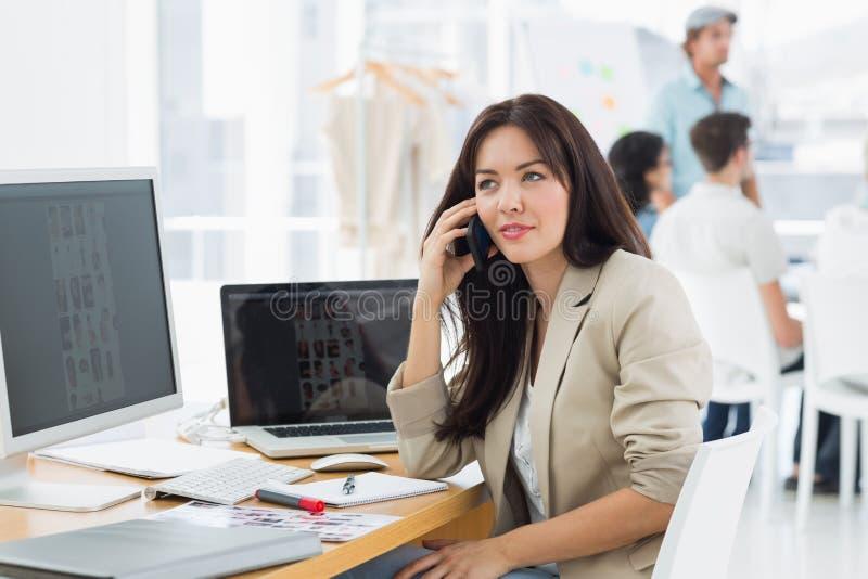 Kvinna på appell på skrivbordet med kollegor bakom i regeringsställning arkivbild