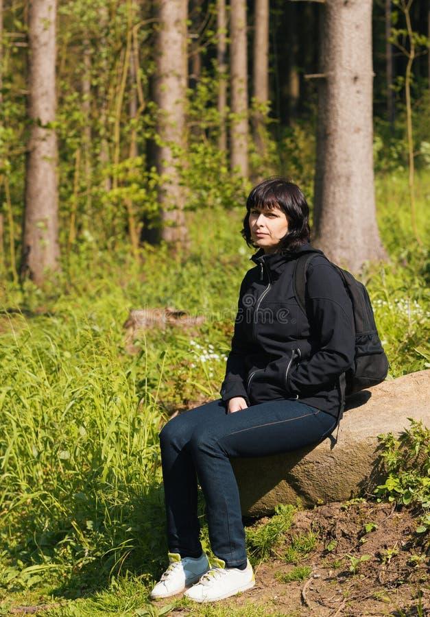 Kvinna på att fotvandra att vila för tur arkivfoton
