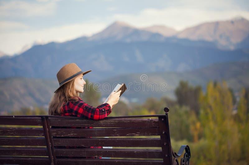 Kvinna på bänken med boken royaltyfria foton