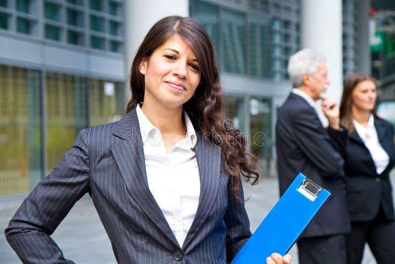 Kvinna på bakgrunden av affärsfolk arkivbild