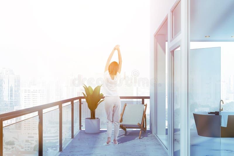 Kvinna på balkong nära badrum royaltyfria bilder