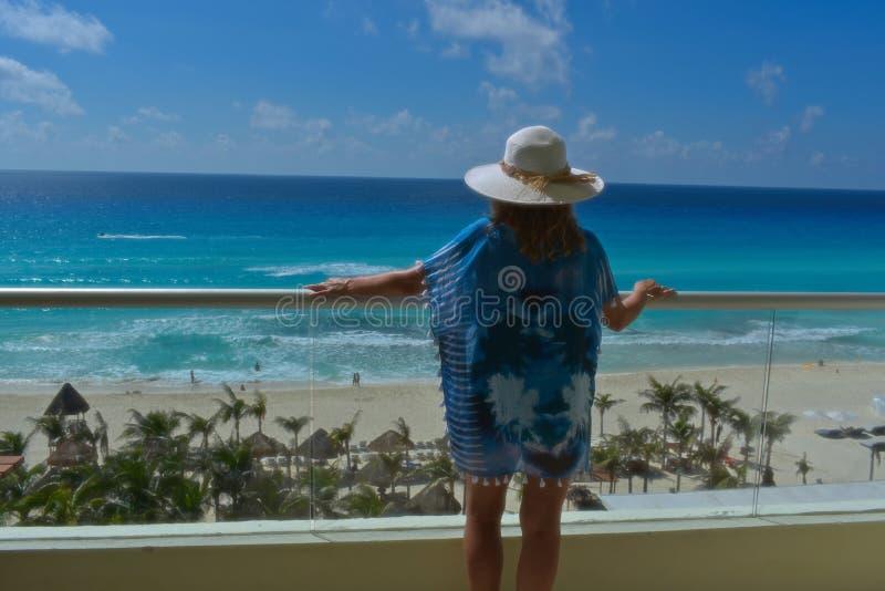 Kvinna på balkongen som ut ser till havet royaltyfri foto