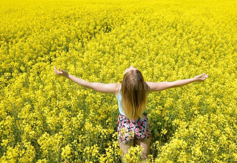 Kvinna på blommande rapsfröfält i vår arkivbild