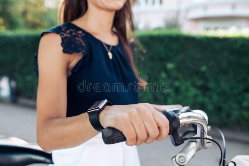 Kvinna på cykeln med en smartwatch royaltyfri foto