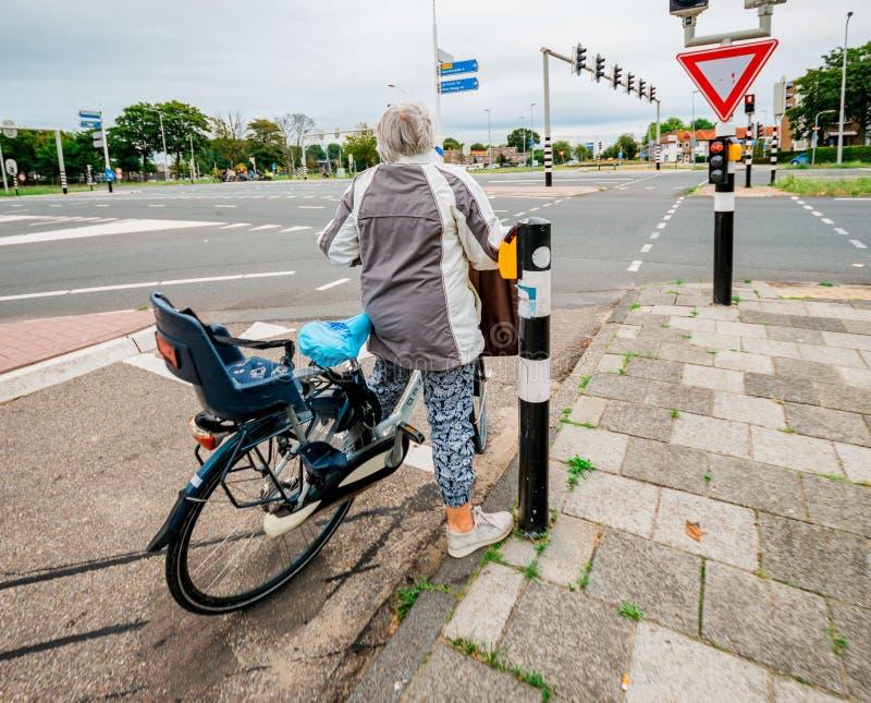 Kvinna på cykeln som väntar för att korsa huvudvägen arkivbilder