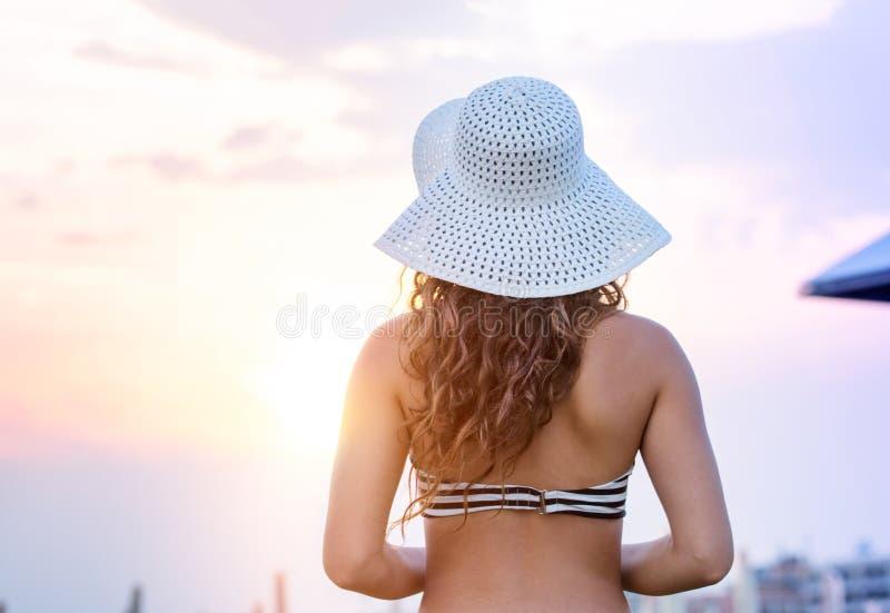 Kvinna på den bärande bikinin för strand och hatten, bakre sikt royaltyfri foto