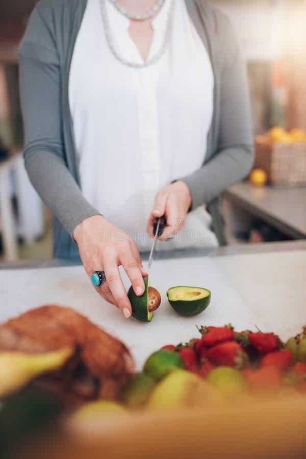 Kvinna på den bitande avokadot för fruktsaftstång royaltyfria bilder