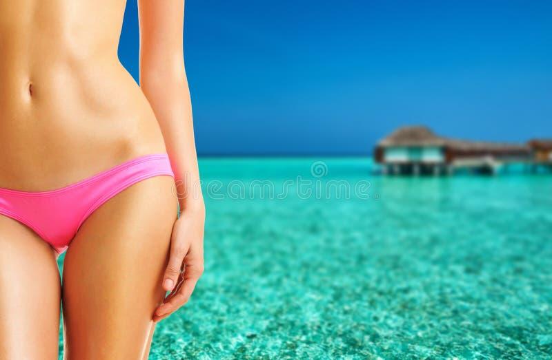 Kvinna på den härliga stranden med vattenbungalower arkivfoto