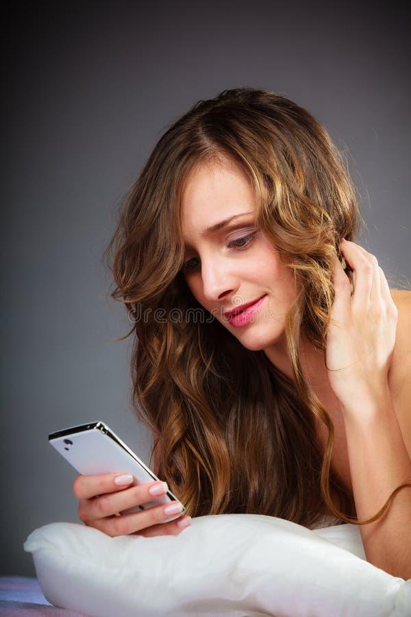 Kvinna på den hållande mobiltelefonen för säng royaltyfria bilder