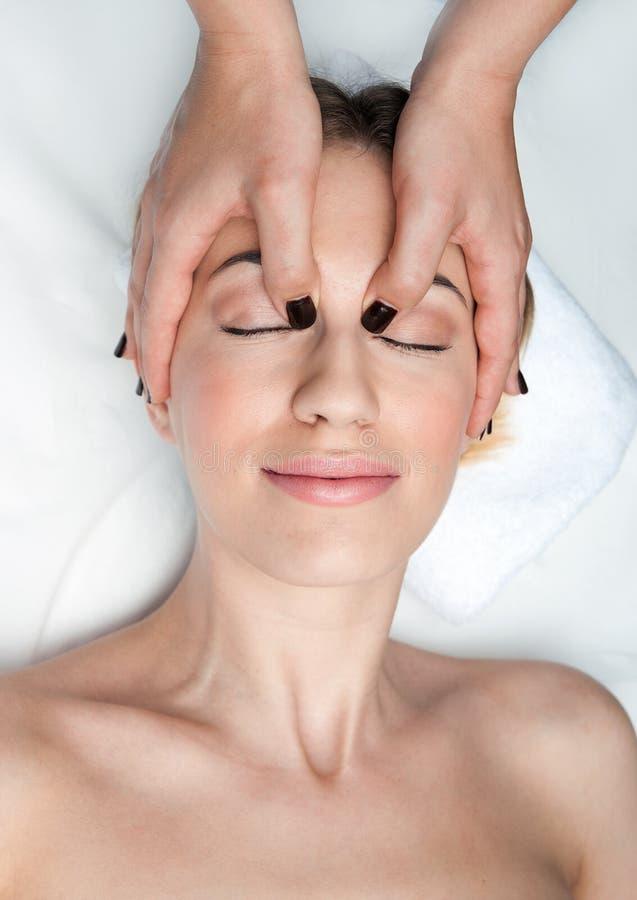 Kvinna på den head massagen i wellness arkivfoton