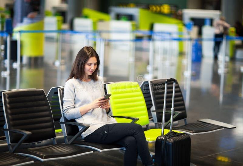 Kvinna på den internationella flygplatsen genom att använda en smartphone royaltyfri bild