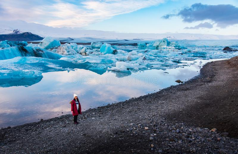Kvinna på den Jokulsarlon glaciärlagun i Island royaltyfria bilder