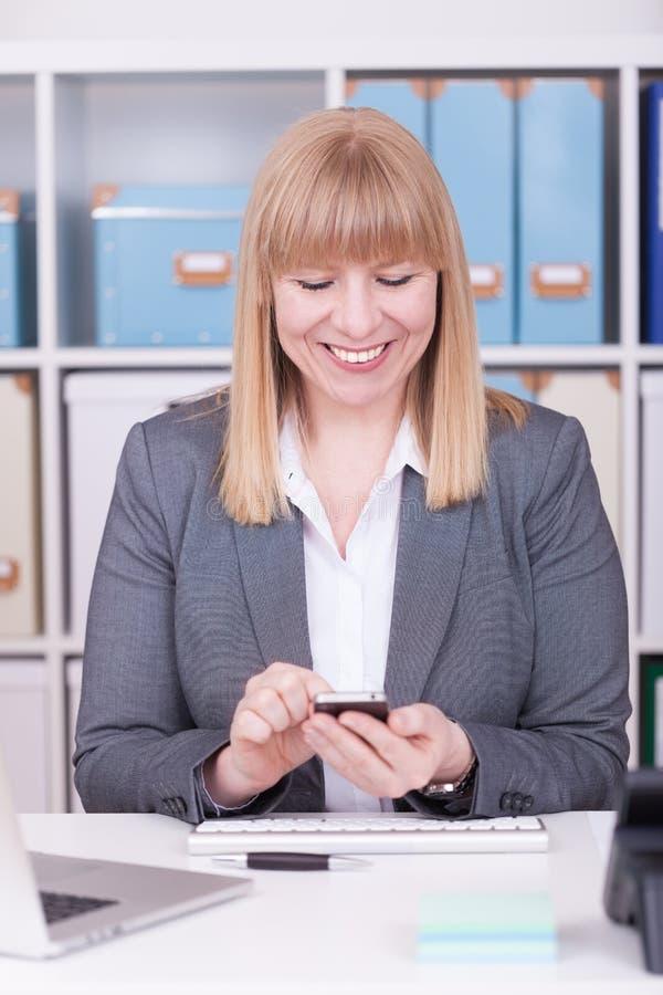 Kvinna på den kontorsmaskinskrivningen och messagingen med hennes mobiltelefon royaltyfri bild