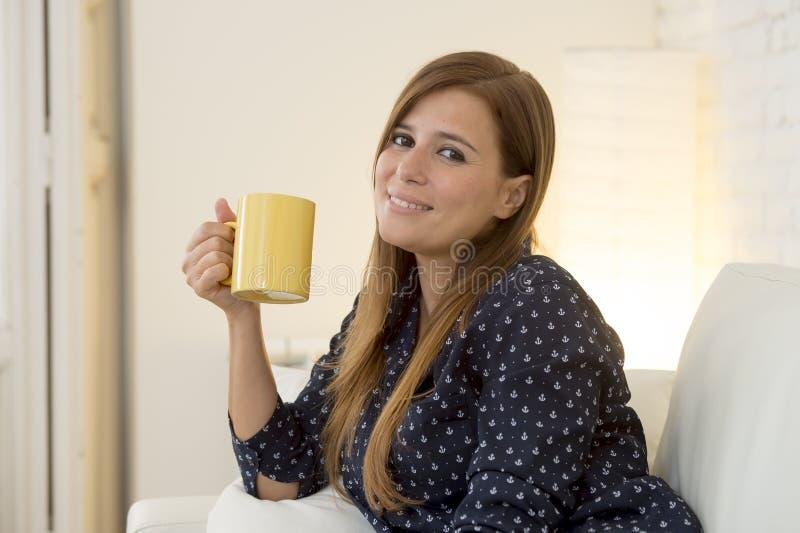 Kvinna på den moderna soffan för lägenhetvardagsrumhem som tycker om kaffetekoppen arkivbild