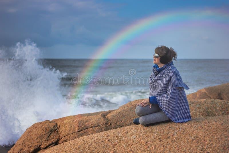 Kvinna på den steniga stranden, regnbåge över det stormiga havet arkivbild