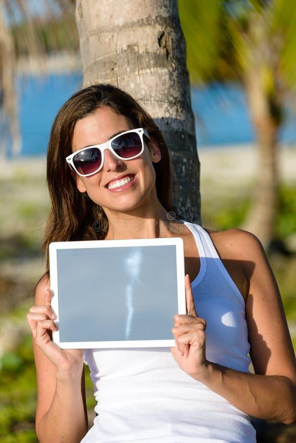 Kvinna på den tropiska semestern som rymmer den digitala minnestavlan arkivfoto