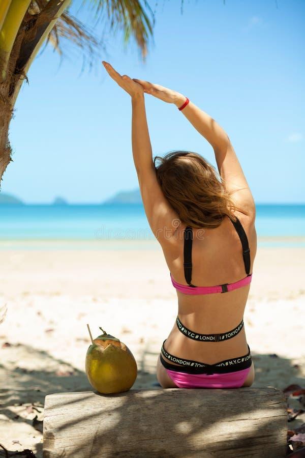 Kvinna på den tropiska stranden med den nya drinken för kokosnöt fotografering för bildbyråer