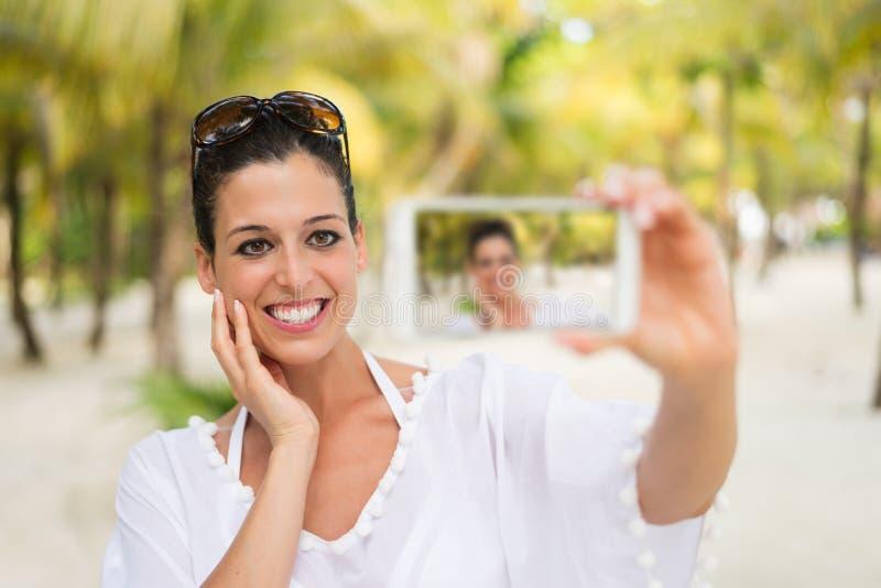 Kvinna på den tropiska strandsemestern som tar smartphoneselfiefotoet royaltyfri bild