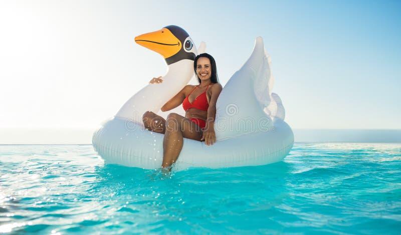 Kvinna p? den uppbl?sbara leksaken i simbass?ng fotografering för bildbyråer