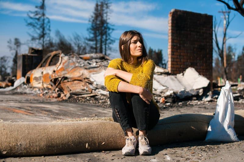 Kvinna på det brända förstörda huset och gården, efter brandkatastrof royaltyfri foto
