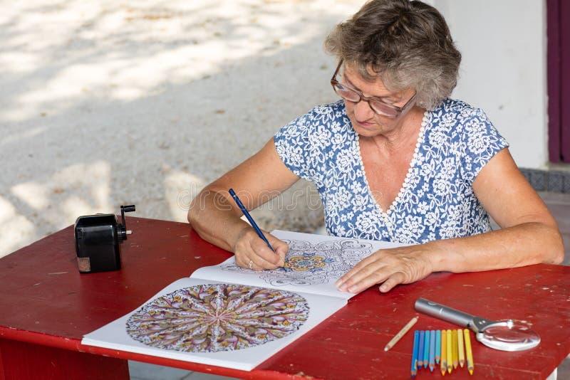 Kvinna på det röda skrivbordet arkivbild