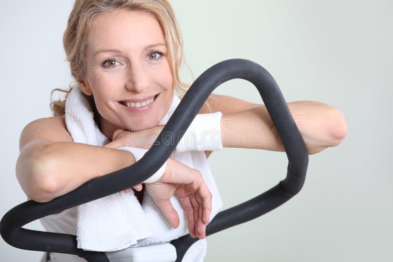 Kvinna på en övningsmaskin royaltyfri bild