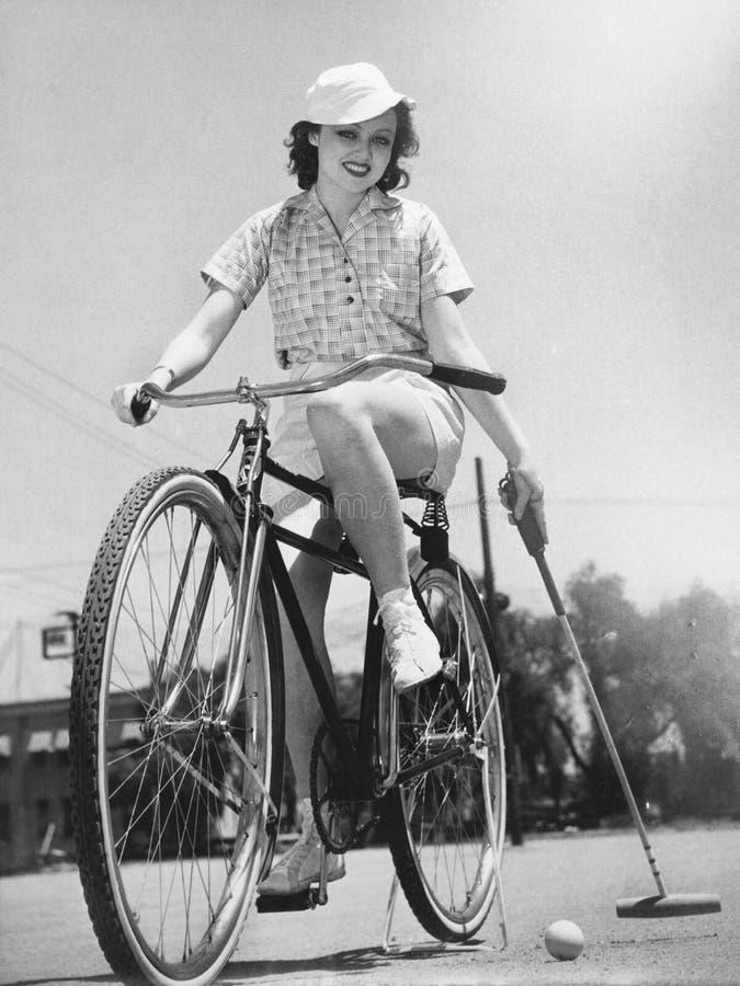 Kvinna på en cykel som spelar polo (alla visade personer inte är längre uppehälle, och inget gods finns Leverantörgarantier som d royaltyfri fotografi